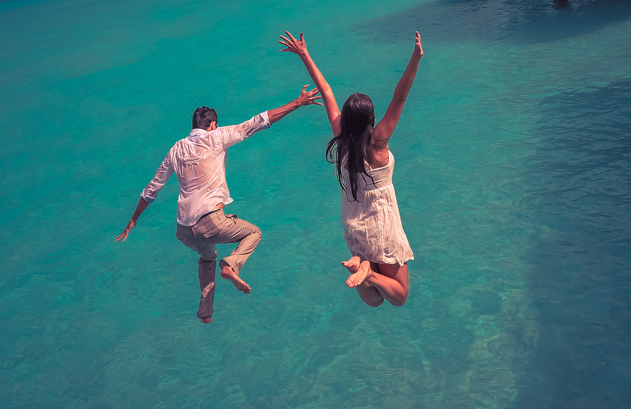 Happiness jump of young couple on the water. Retro style color tones.