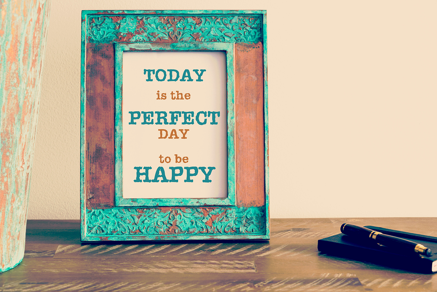 Retro effect and toned image of a vintage photo frame next to fountain pen and notebook . Motivational quote written with typewriter font TODAY IS THE PERFECT DAY TO BE HAPPY