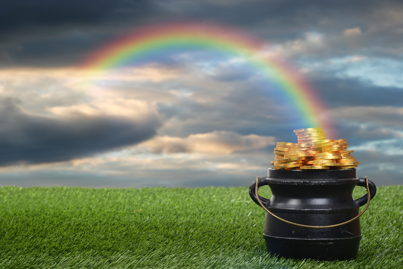 closeup of pot of gold with rainbow with cloudy sky
