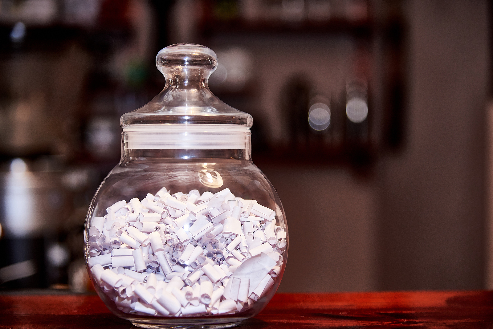 Glass jar with predictions stands on a wooden table.Copy space
