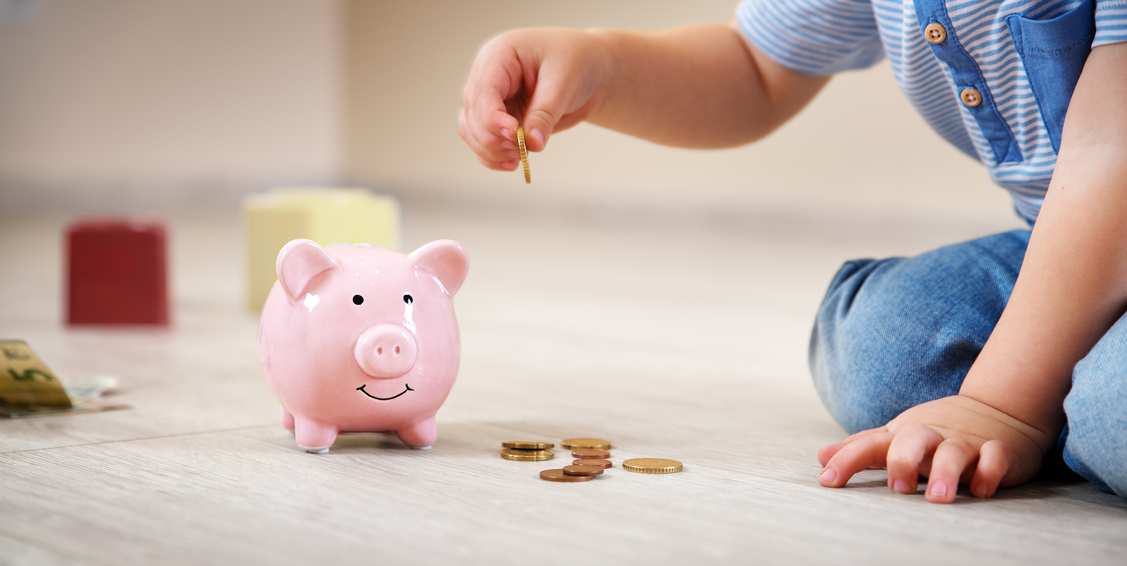 two years old child sitting on the floor and putting a euro coin into a piggybank.