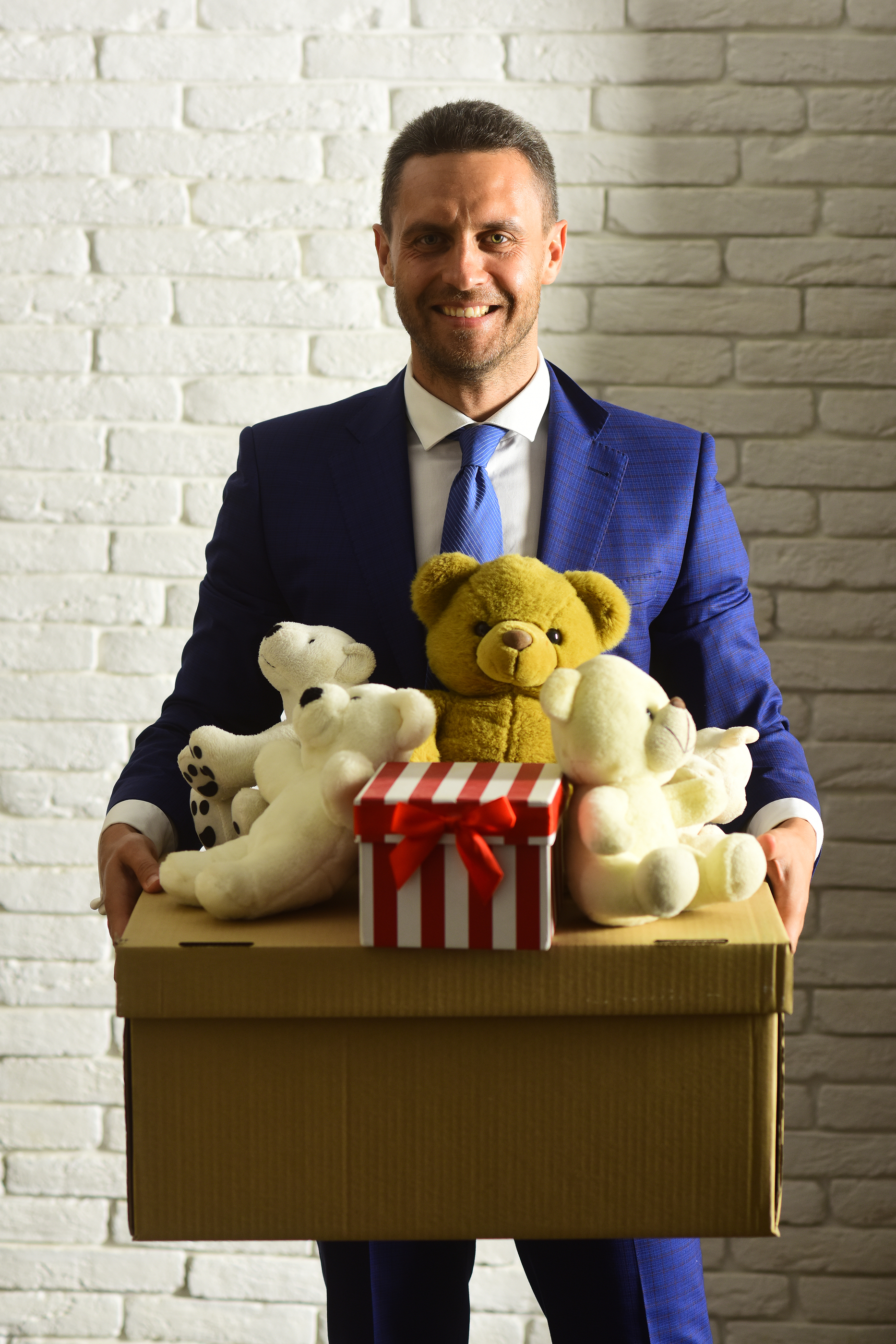 Businessman wears smart suit and tie. Business and volunteering concept. Executive holds box full of toys and Christmas present on white brick wall background. Man with smiling face makes donation.
