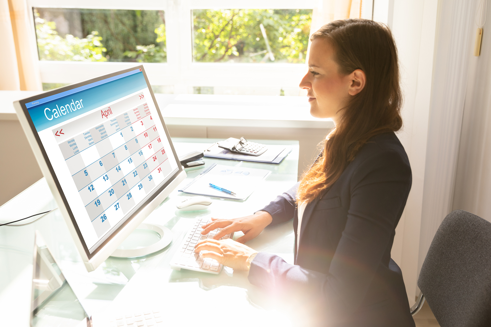 Young Businesswoman Looking At Calendar On Computer Screen Over Desk